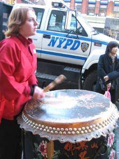 Another Drummer walks along on Canal Street within NYC's Chinatown.