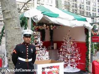 A US Marine guards over the Toys for Tots Box as we welcomes all.