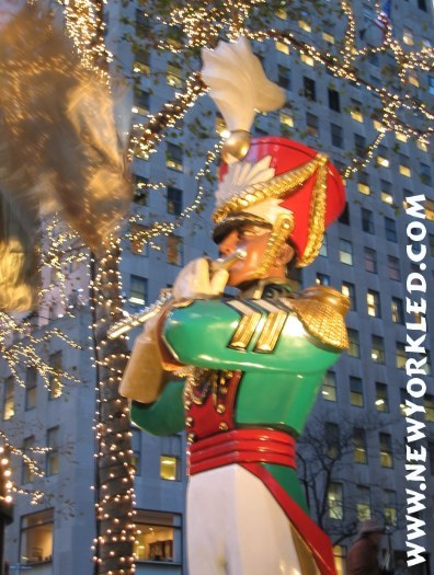 Photo of a soldier and his flute at Rockefeller Center during Christmas time.