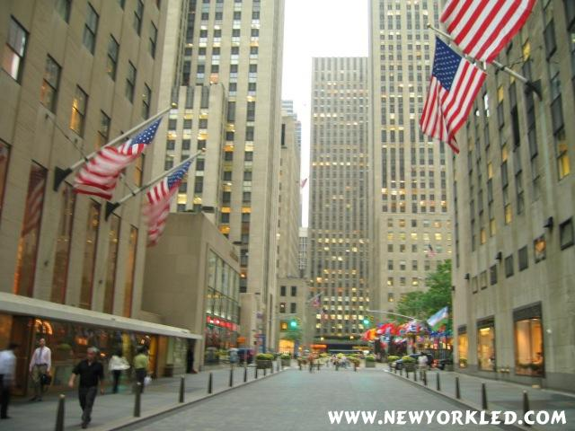 We're facing north along Rockefeller Plaza as the American Flags hang overhead in this photo.