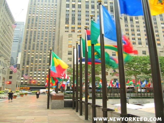 The international Flags of the world fly in the air over and above the Rink at Rockefeller Center.