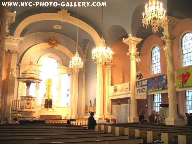 This photo features the columns, chandeliers and pews found within St. Paul's Chapel.